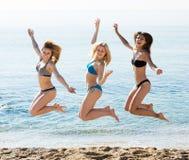 Three girls jumping on beach stock photos
