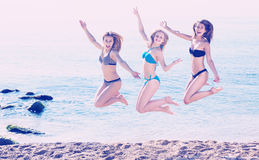 Three girls jumping on beach royalty free stock photos
