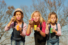 Three girls kids sisters blowing bubbles with soap in a farm fie Stock Images