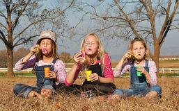 Three girls kids sisters blowing bubbles with soap in a farm fie Stock Image