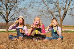 Three girls kids sisters blowing bubbles with soap in a farm fie Royalty Free Stock Image