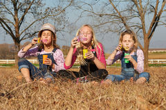 Three girls kids sisters blowing bubbles with soap in a farm fie Royalty Free Stock Photo