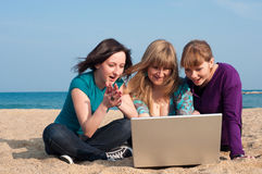 Three girls with a laptop. On a beach Royalty Free Stock Photo