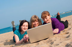 Three girls with a laptop. On a beach Stock Photo