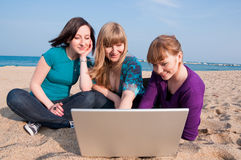 Three girls with a laptop. On a beach Stock Image
