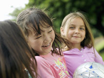 Three girls (7-9) laughing, one girl with soccer ball, close-up, portrait (differential focus) Royalty Free Stock Images