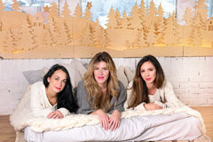 Three girls laying on the bed in cozy sweaters smiling Royalty Free Stock Images