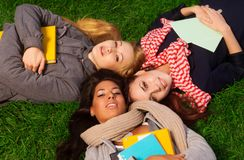 Three girls laying in park Stock Image