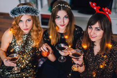 Three girls looking at camera at a home party Stock Photo