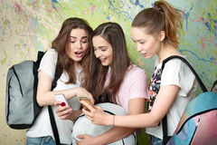 Three girls are looking at the phones Stock Photography
