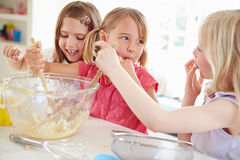Three Girls Making Cupcakes In Kitchen Royalty Free Stock Photos