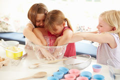 Three Girls Making Cupcakes In Kitchen Stock Image