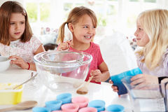 Three Girls Making Cupcakes In Kitchen Stock Photos