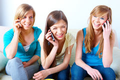 Three girls with mobile phones stock images