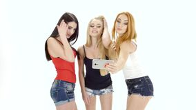 Three girls of model appearance make selfie to camera smartphone stock video footage
