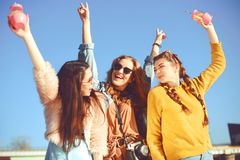 =Three girls near the river against the sky having fun. Fashion girls in sunglasses. Jump, rejoice, drink drinks, smile have fun royalty free stock image