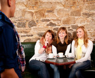 Three girls and one man in bar. Man just arrived in a caffee where three girls were expecting him Royalty Free Stock Photography