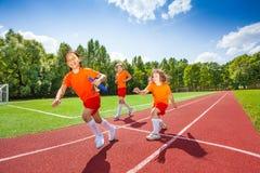 Three girls with one relay baton running Royalty Free Stock Image
