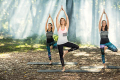 Three girls perform body balance exercises in nature royalty free stock photo