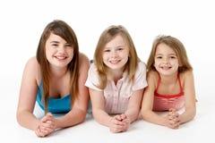 Three Girls Piled Up In Pyramid In Studio Stock Photo