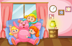 Three girls and pink teddy bear in living room Stock Photo