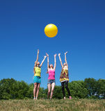 Three girls play with yellow ball Royalty Free Stock Photography