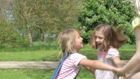Three Girls Playing Ring-Around-The-Rosy Outdoors Stock Photo