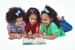 Three girls reading a book. Against a white background Stock Photography