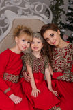 Three girls in a red evening dress the Christmas tree. Stock Image