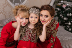 Three girls in a red evening dress the Christmas tree. Royalty Free Stock Photos
