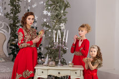 Three girls in a red evening dress the Christmas tree. Royalty Free Stock Image