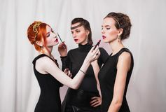 Three girls with red lips in black dress doing makeup woman with earrings and ornaments on head, Stock Images