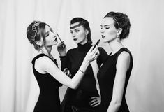 Three girls with red lips in black dress doing makeup woman with royalty free stock image