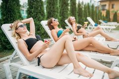 Three girls relax and sunbathig on deck chairs Stock Photo