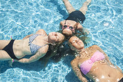 Three girls relaxing in the pool Royalty Free Stock Images
