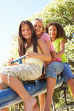 Three Girls Riding On See Saw In Playground. Smiling At Camera Royalty Free Stock Image