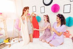 Three girls with curlers in their hair coosing between two dresses. They are celebrating women`s day March 8. stock photography