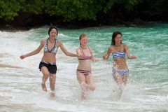 Three girls run on the beach Royalty Free Stock Images