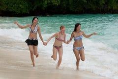 Three girls run on the beach Stock Photography