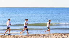Three girls run on the beach Stock Photo