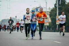 Three girls runners run through streets of city Stock Photography