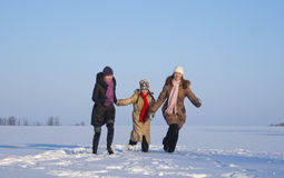 Three girls running. On the snowy field Royalty Free Stock Image