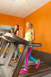 Three girls running in the gym on treadmill Royalty Free Stock Photo