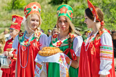 Three girls in Russian folk costumes is waiting for guests with Royalty Free Stock Photo
