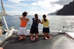 Three Girls on a Sailboat in Kauai. Three girls gaze at the pretty view while sailing in in Hawaii off the coast of the island of Kauai Stock Image