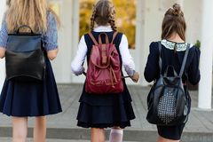 Three girls in school uniform with backpacks stand on the steps Royalty Free Stock Image