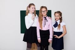 Three girls schoolgirl in glasses at the blackboard on the lesson at school royalty free stock photo