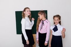 Three girls schoolgirl is standing at the Blackboard with lesson stock photo