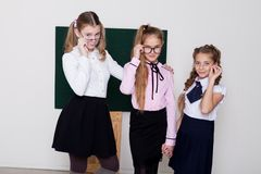 Three girls schoolgirl is standing at the Blackboard with lesson royalty free stock photography