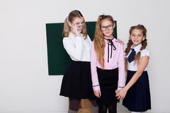 Three girls schoolgirl is standing at the Blackboard with lesson stock image